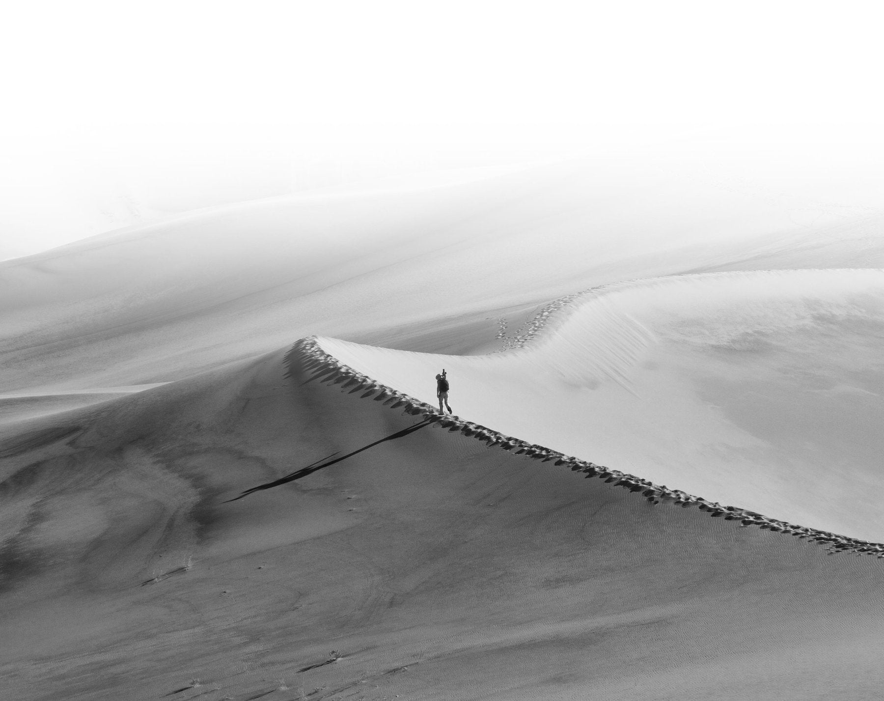 Peter Lik walking across the Mesquite Flat Sand Dunes in Death Valley National Park in California.