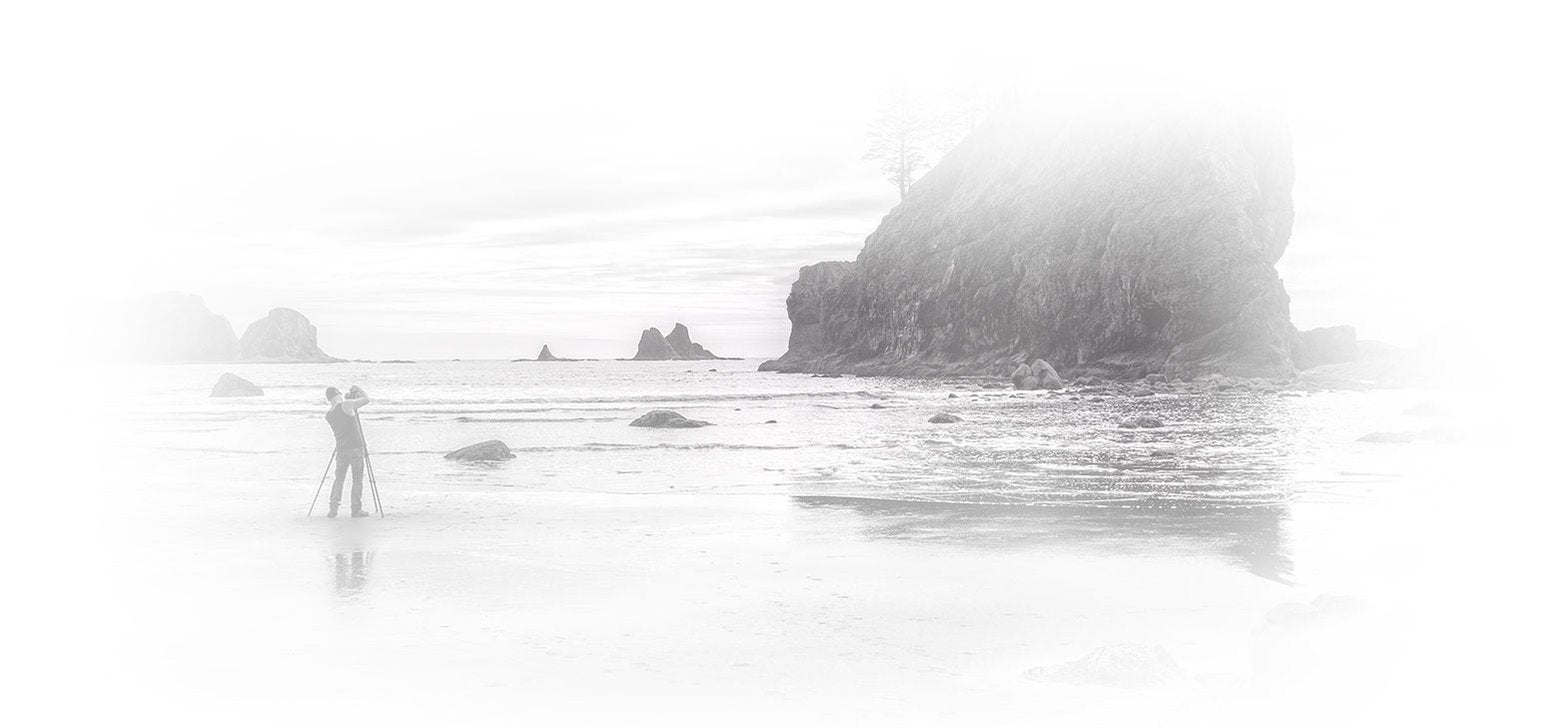 Portrait of Peter Lik taking a photograph on the beach in La Push, Washington.