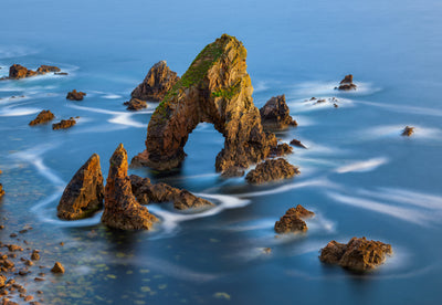 Ocean photographs of the tide swirling off rock formations on the coast of Ireland