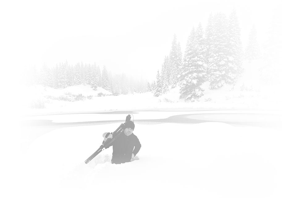 Black and white portrait of Peter Lik standing waist deep in the snow with a tripod and camera over his shoulder