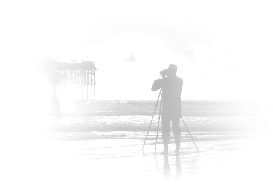 Silhouetted black and white portrait of Peter Lik taking a photograph of the Huntington Beach Pier in California