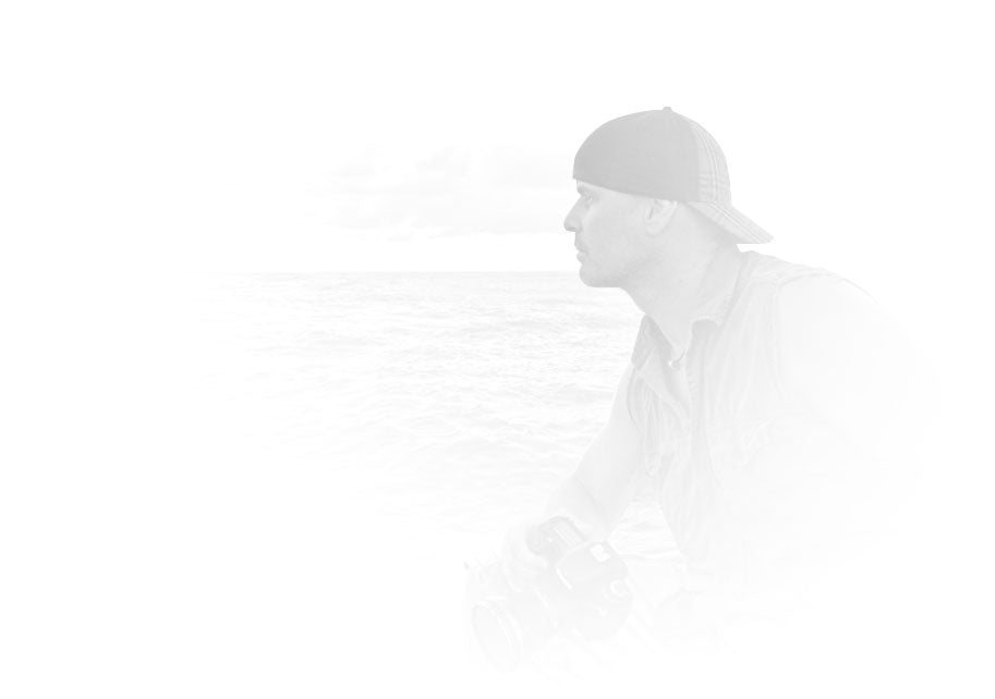 Black and white portrait of Peter Lik in a sleeveless shirt and baseball cap sitting on back of boat looking out at Pacific Ocean