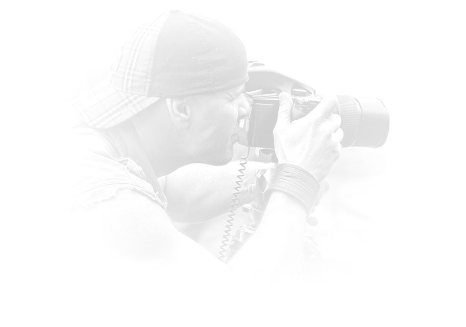 Portrait of Peter Lik wearing a sleeveless shirt and baseball cap taking a photograph with a Phase One camera