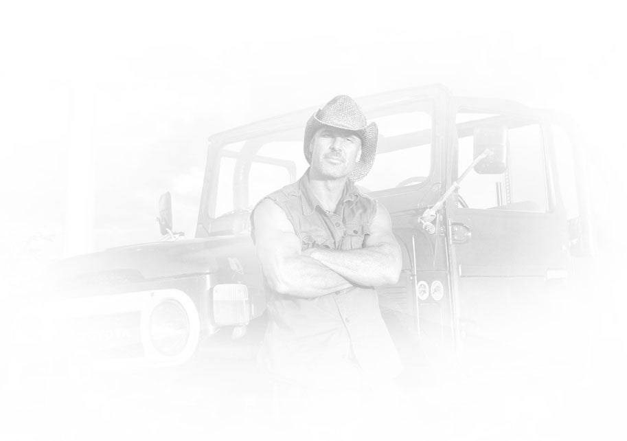 Black and white portrait of Peter Lik wearing a sleeveless shirt and cowboy hat leaning on a Jeep Wrangler