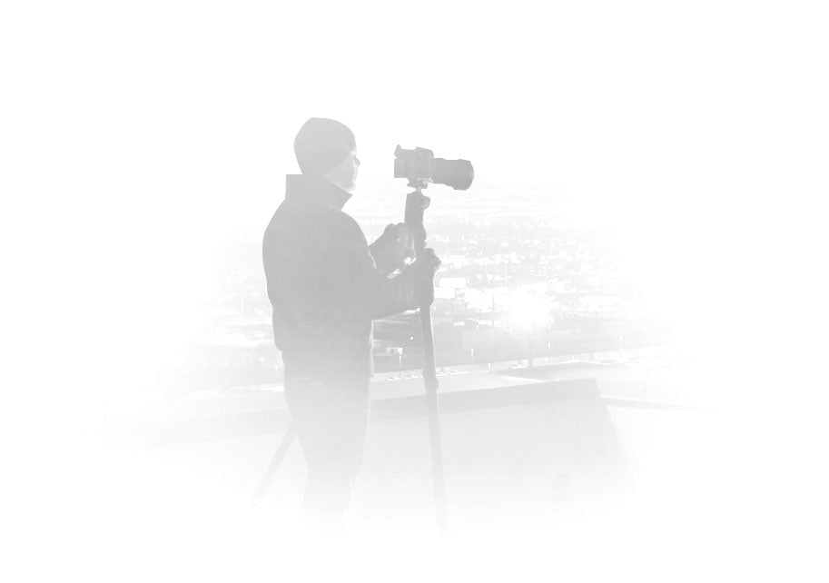 Silhouetted portrait of Peter Lik wearing a jacket and beanie taking a photograph with a camera on a tripod