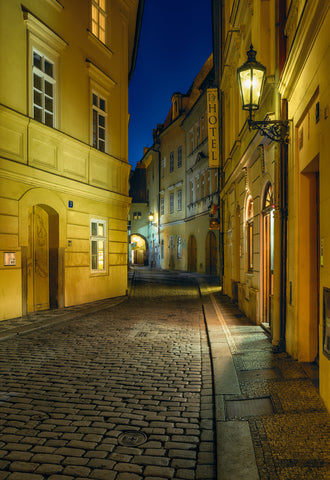 Cobblestone streets of Venice Italy lit by the yellow glow of street lamps at night