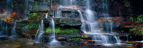 Waterfall pouring over moss covered black rock wall into a pond in the Blue Mountains National Park Australia