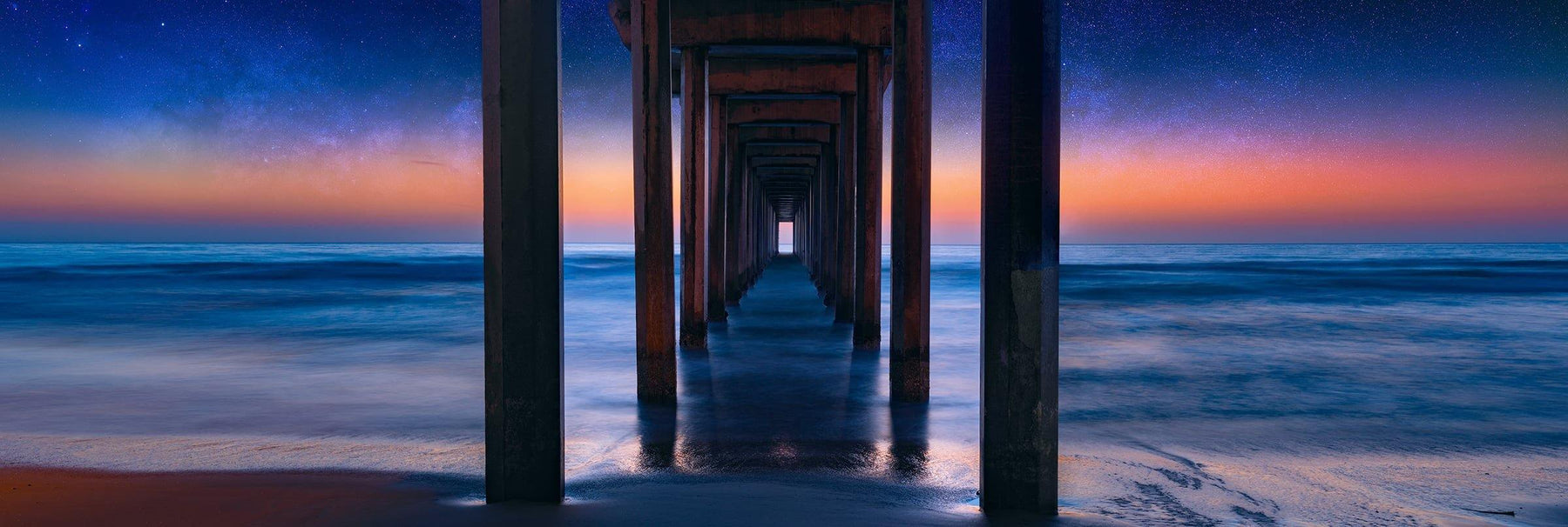 The ocean and Scripps Pier of La Jolla California with the glowing horizon and star filled sky in the background