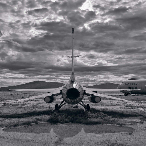 Black and white back view of an old F-16 on a grass and dirt field in Tucson Arizona