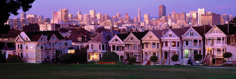 Row of Victorian houses across from a grass area with the skyscrapers of San Francisco in the background