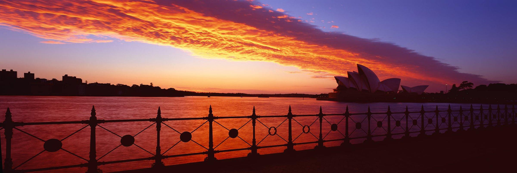 Rod iron fence at the edge of Sydney Harbor during the sunset glow with Sydney Opera House in the background