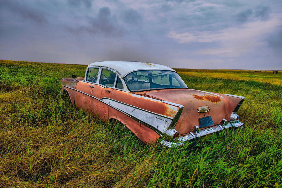 Old rusty red and white car in a grass field in North Dakota during a storm
