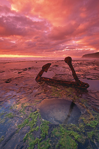 Rusty old anchor on its side in the shallow tide pools off the coast of the Great Ocean Road Australia