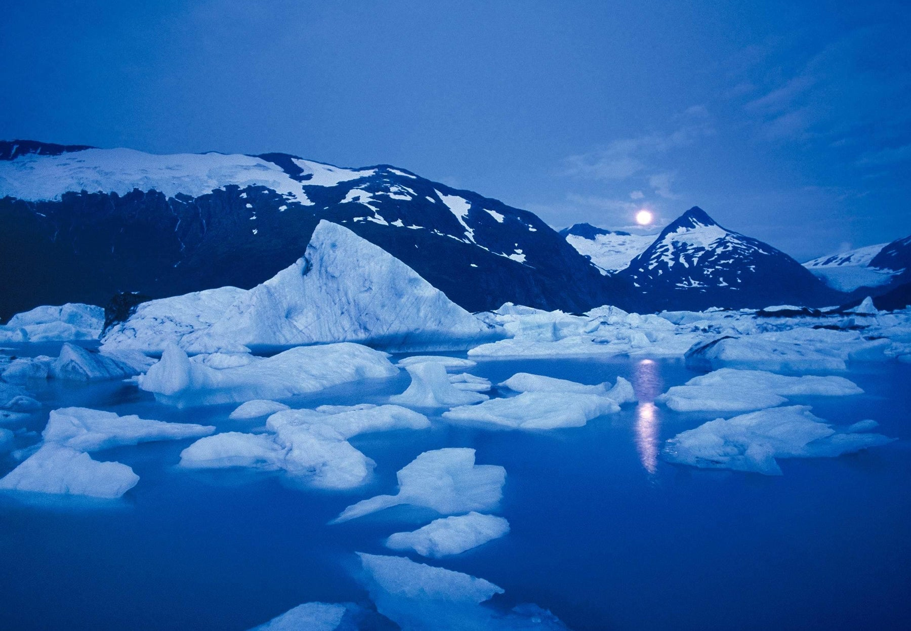 Moon in the sky over the mountains shining onto Portage Glacier and the ice chunks floating in Portage Lake Alaska