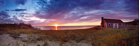 Sun setting on the ocean behind a red cottage on the grass covered beach of Cape Cod Massachusetts