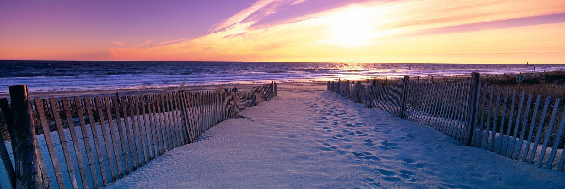 Sand pathway with picket fences leading to a beach in Newport Rhode Island during sunrise