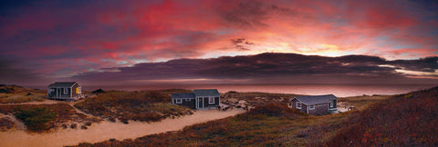Three shacks spread out along the grass brush and sand beaches of Cape Cod Massachusetts at sunset