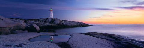 Reflection of Peggy's Cove Lighthouse in a puddle on the rocky coastline of Nova Scotia