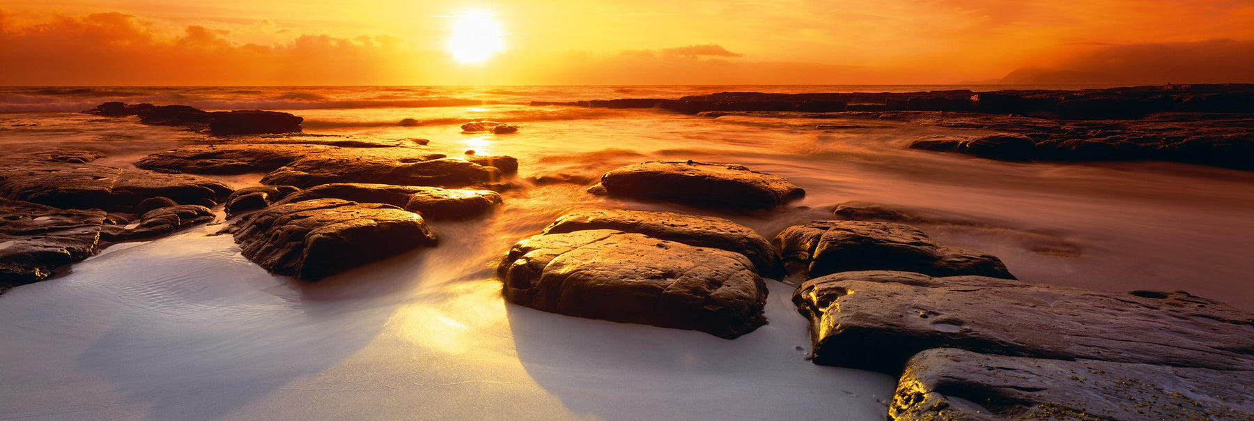Rocks on a sandy beach during low tide at Wineglass Bay Australia with the sun rising in background