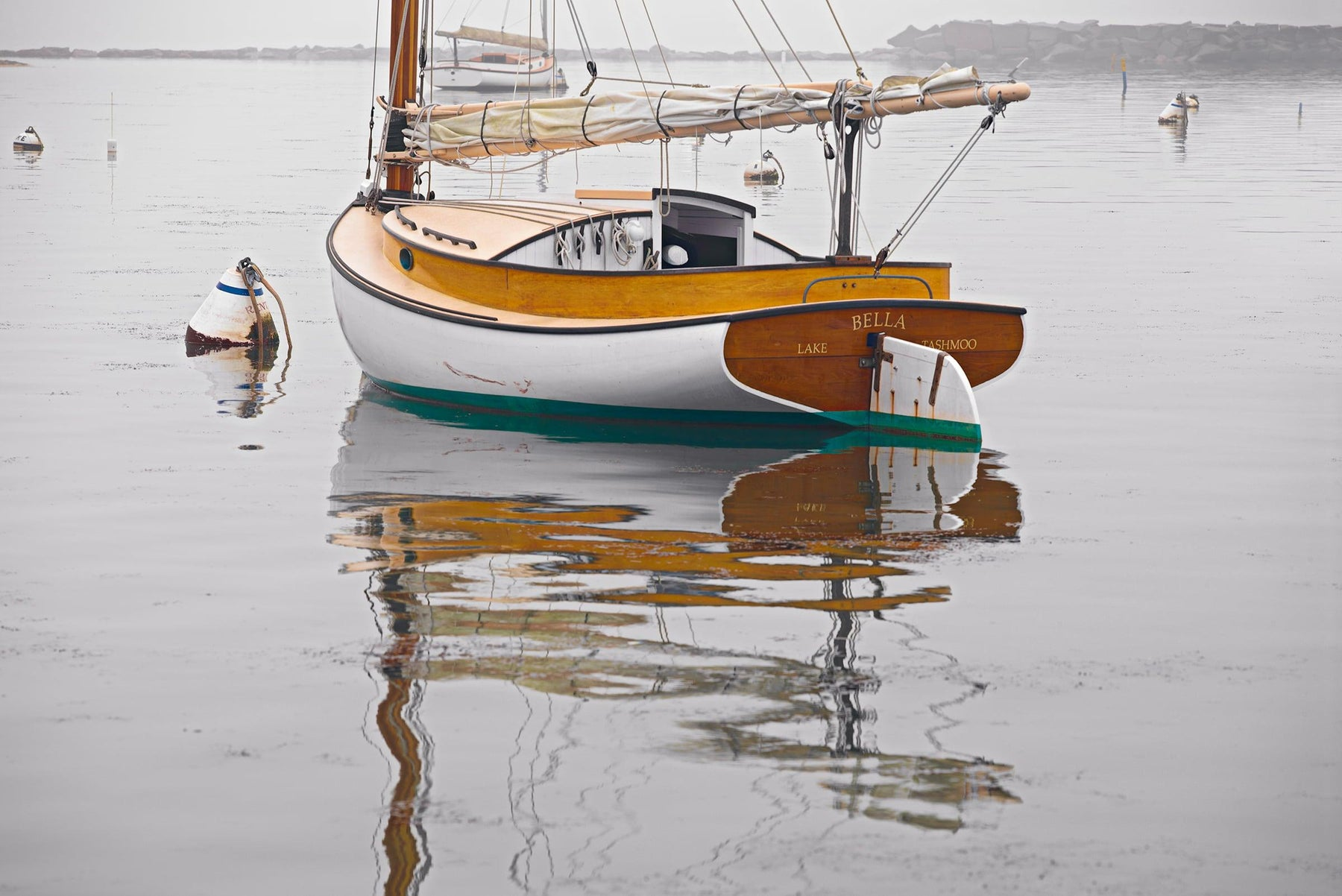 Sail boat and buoy reflecting off the water in a fog filled harbor in Martha's Vineyard Massachusetts