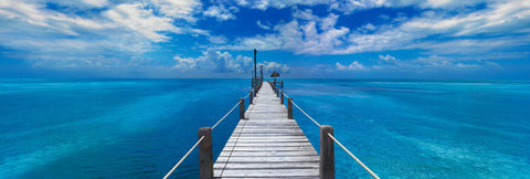 White washed wooden Jetty with rope handrails reaching out over the turquoise ocean in Key West Florida