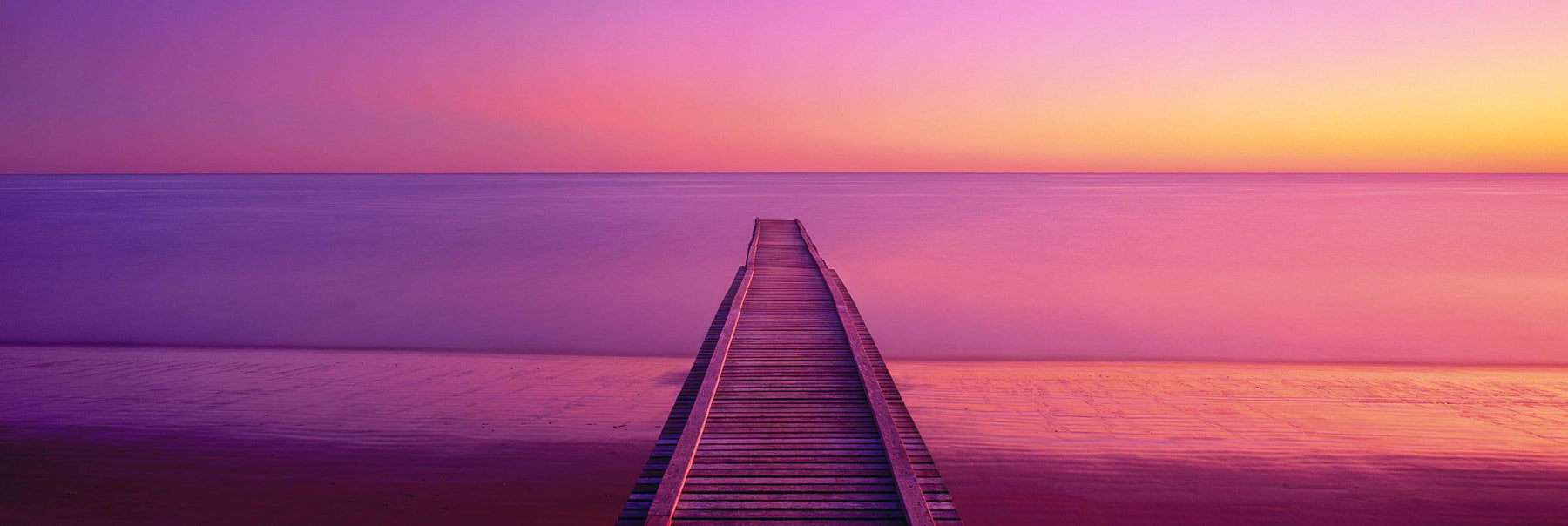 Timber Jetty stretching out into the ocean at Hervey Bay Australia during a pink sunrise