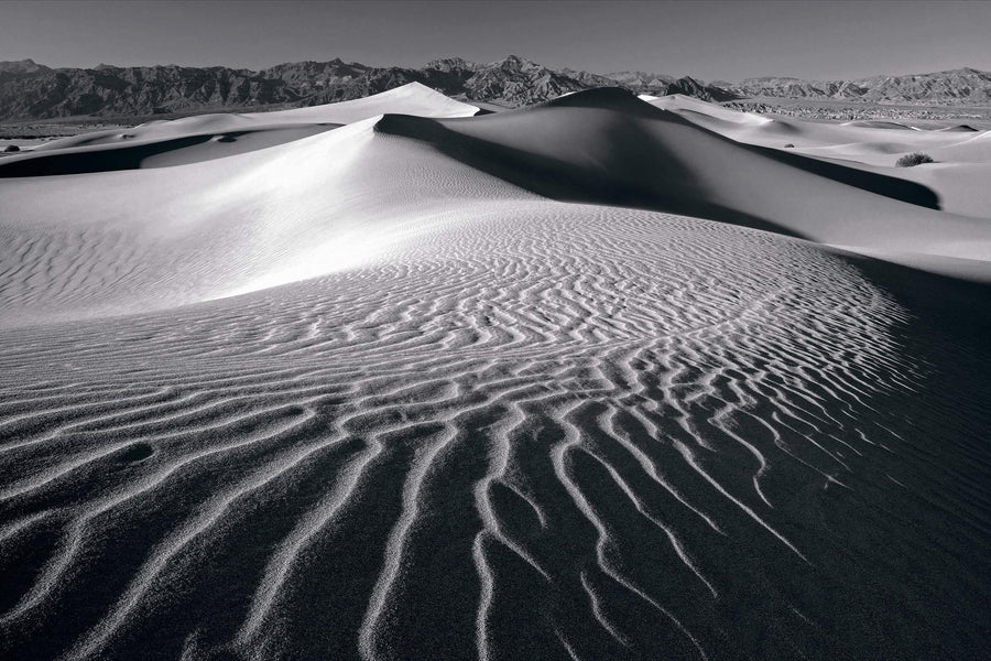 Black and white windswept sand dunes of Death Valley California with rock hills in the distance