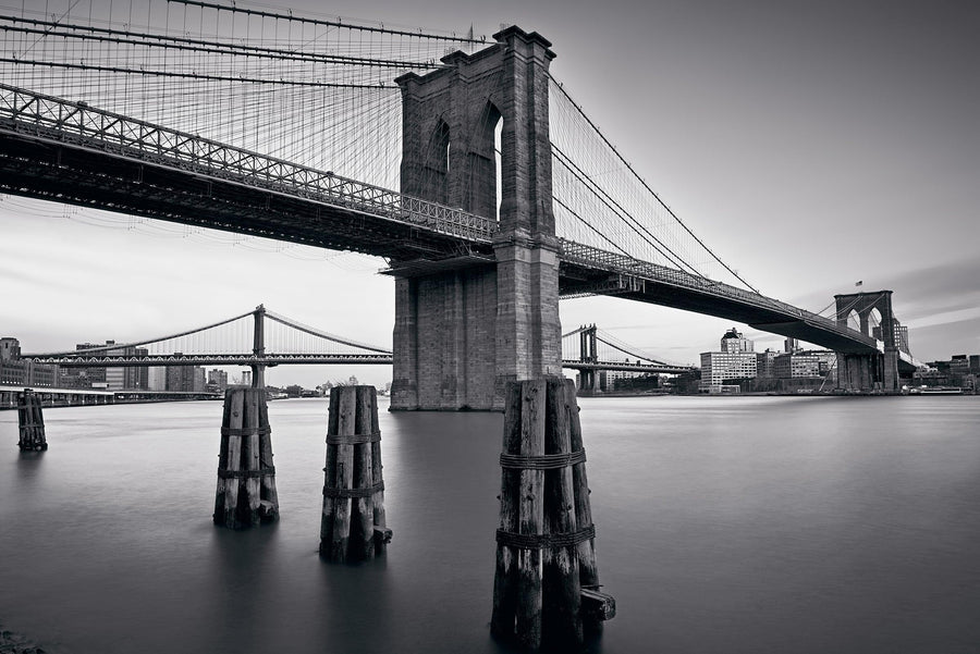 Black and white Brooklyn Bridge from the waters edge with the Manhattan Bridge and New York City in the background