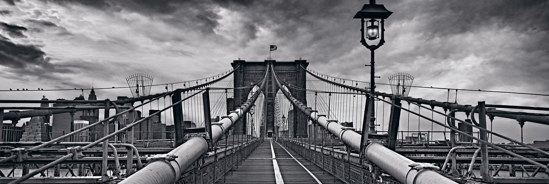 Black and white wooden path leading down the middle of the Brooklyn Bridge New York