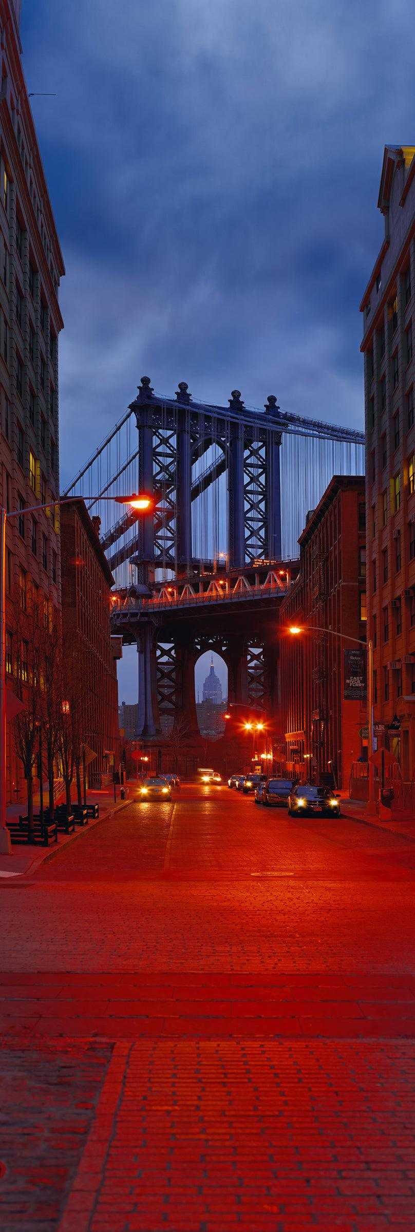 New York City street full of cars at night leading to the Manhattan Bridge