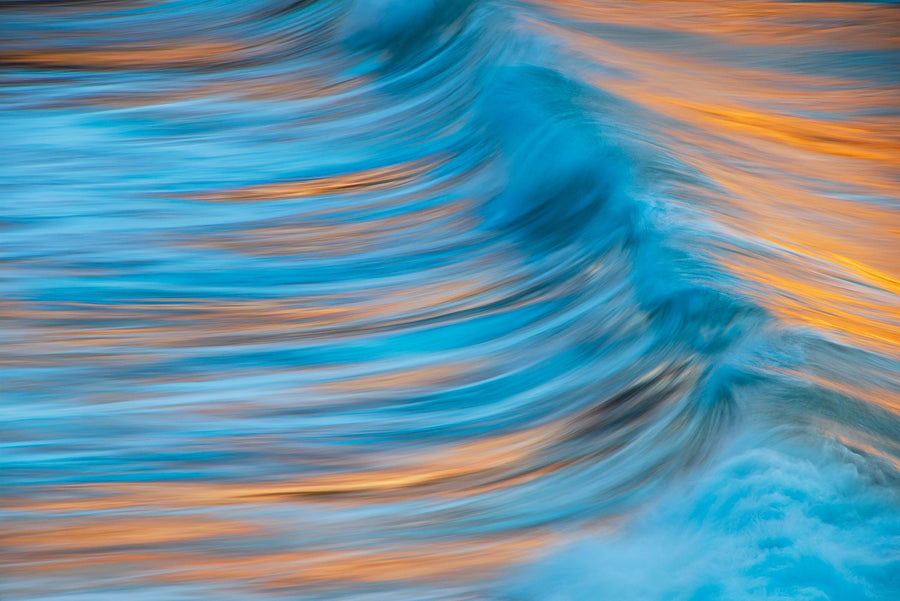 Close up of a turquoise wave reflecting orange from the sun during a sunset in Maui Hawaii