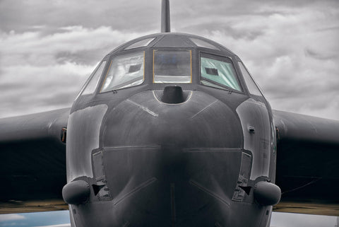 Close up of the front of a B-52 Bomber airplane with storm clouds in the background