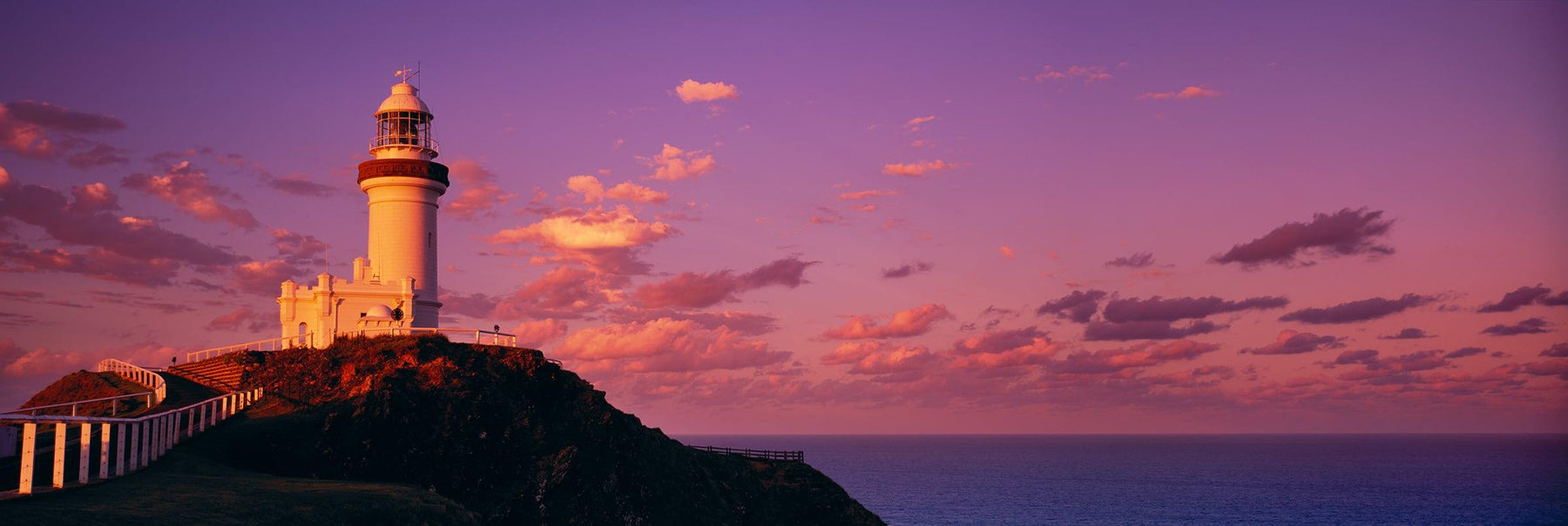 Cape Byron Lighthouse on a coastal cliff looking over the ocean at Byron Bay Australia at sunrise