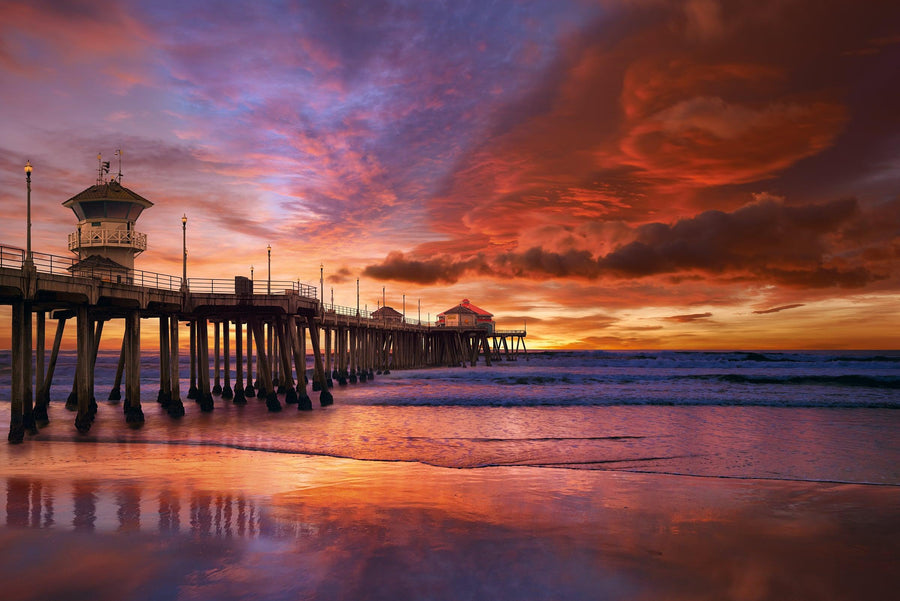 Huntington Beach Pier leading over the ocean under a red cloudy sky at sunset