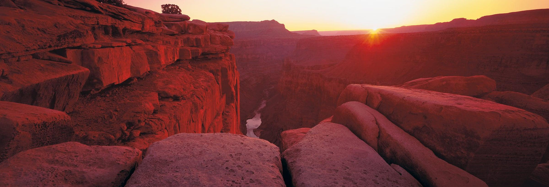 Edge of a rock cliff looking down at the Colorado River at the bottom of the Grand Canyon Arizona at sunrise