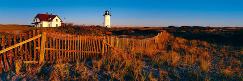 Wooden picket fence in front of a house and lighthouse on the brush covered coast of Cape Cod Massachusetts