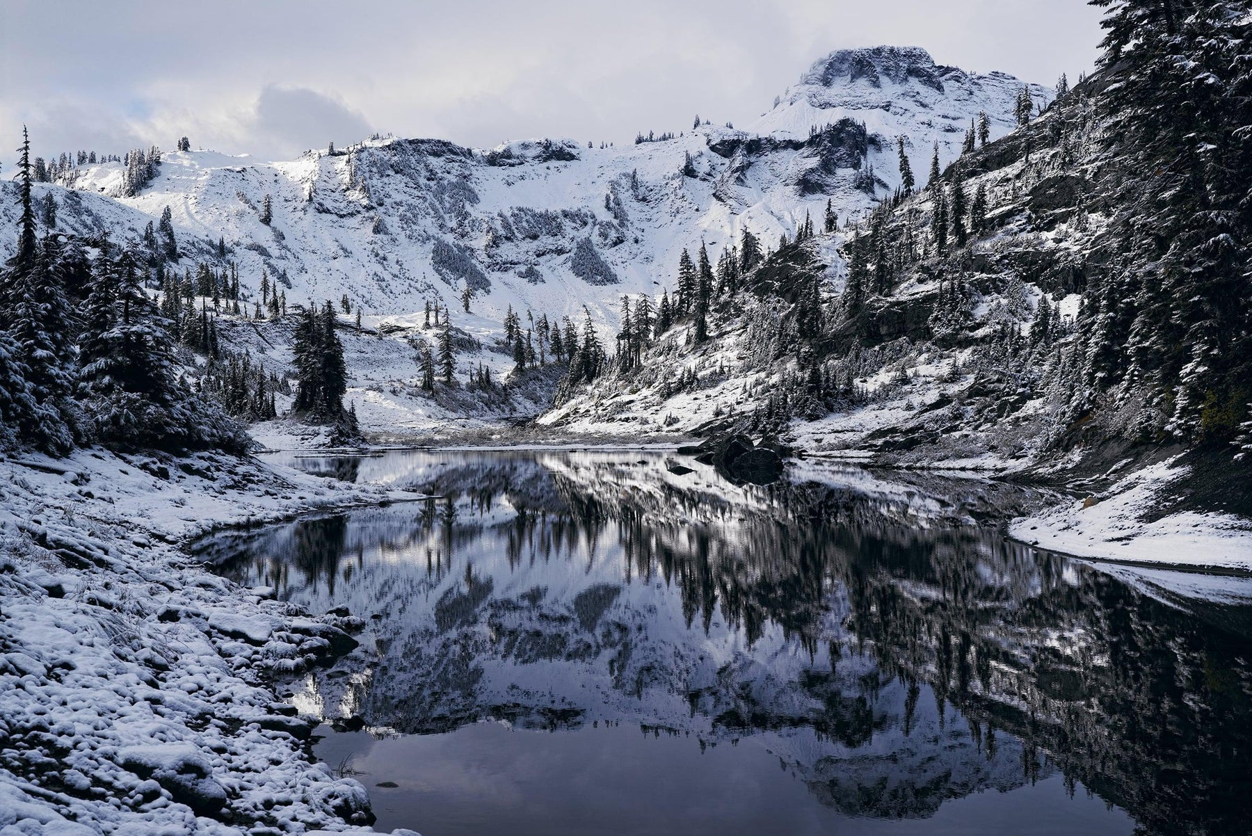Snow covered shoreline and forest surrounding the a lake in front of Mount Baker Washington