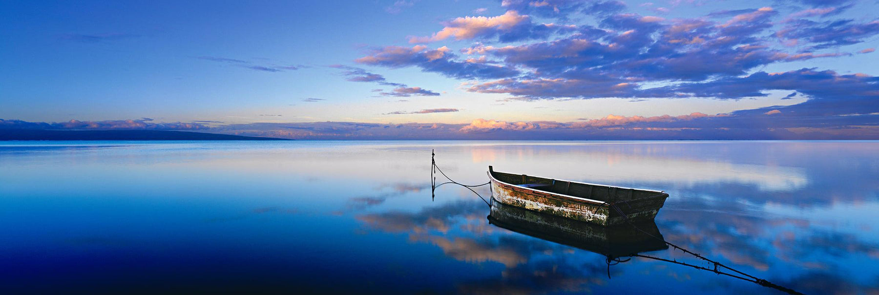Old rowboat tied up on the perfectly still waters of the shoreline of Molokai Hawaii under a cloud filled sky