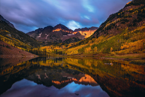 Autumn colored Maroon Bells mountainside and storm clouds overhead reflecting off of Maroon Lake Colorado