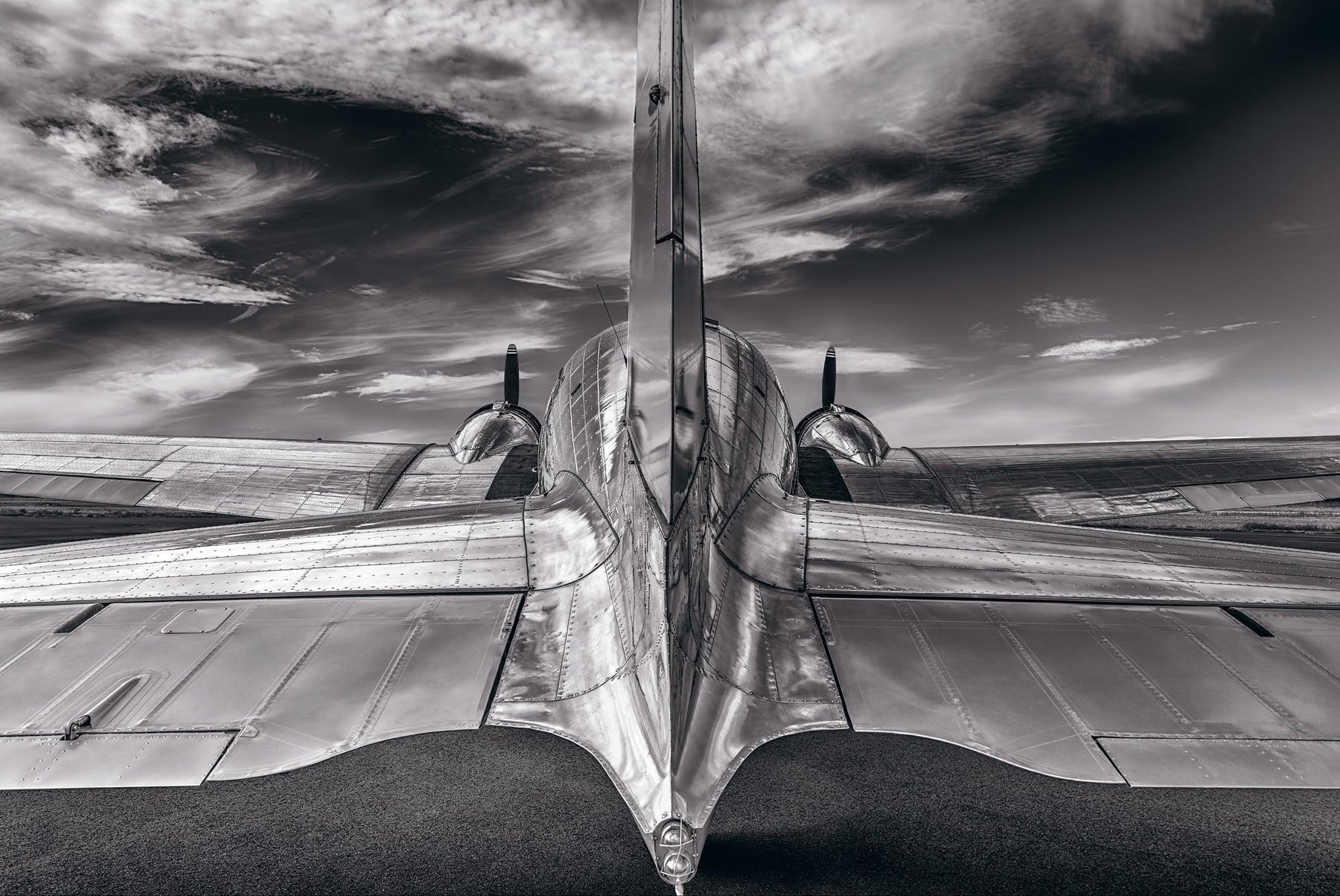 Black and white back view of a DC-3 airplane on a runway in Aurora Oregon looking out to a cloudy sky