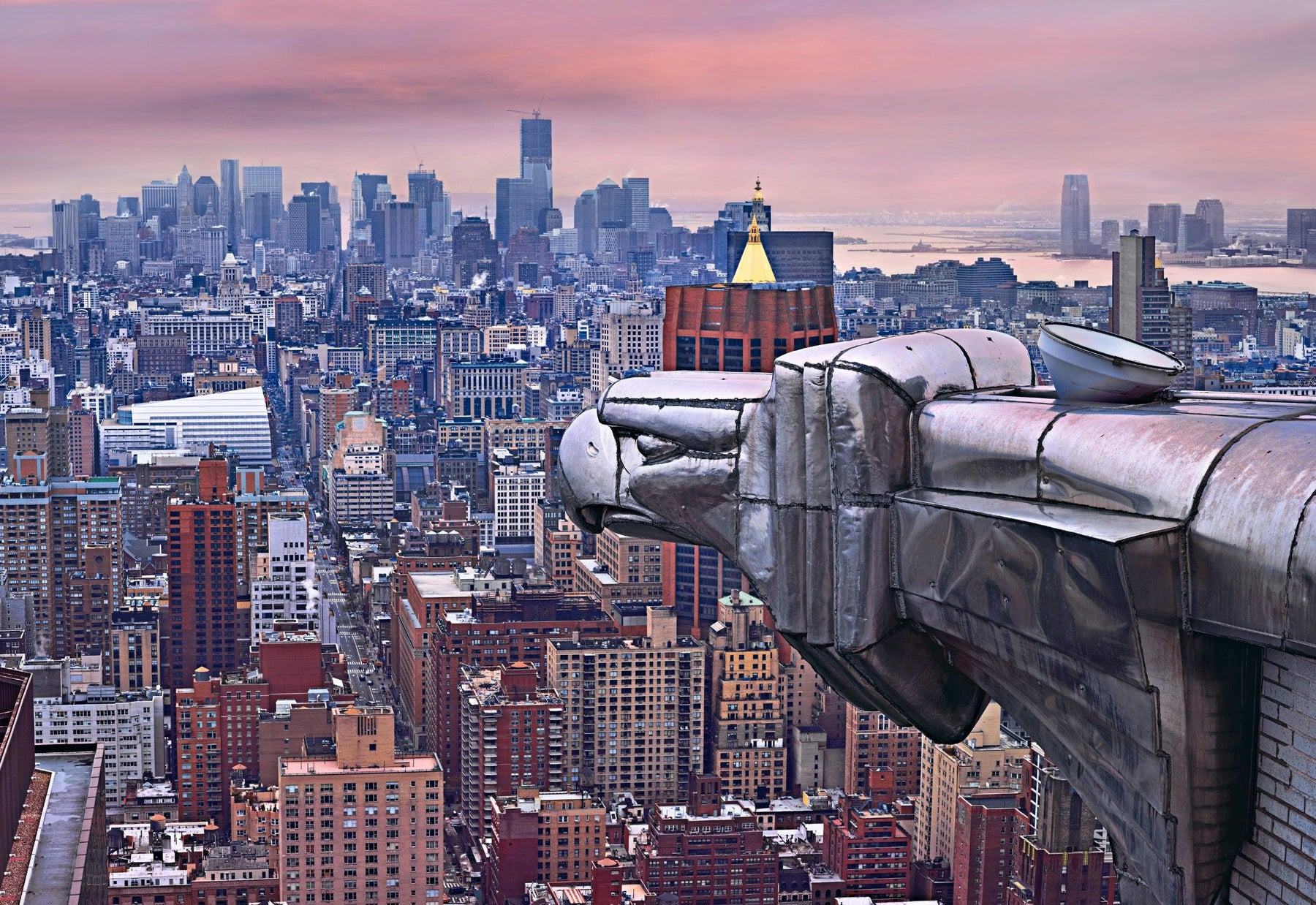Metal eagle head statue overlooking the city of New York on a cloudy day at sunset