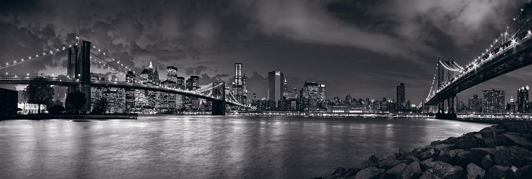 Black and white rocky rivers edge looking across to the lit up bridges leading into the New York cityscape