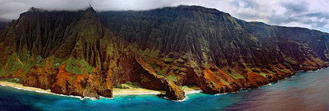 Aerial view of the grass covered cliff shoreline of Na Pali Coast Hawaii dropping into the ocean