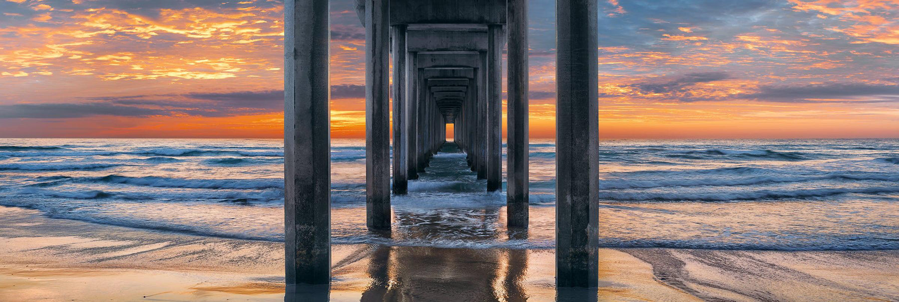 Waves crashing onto the beach and Scripps Pier in La Jolla California at sunset
