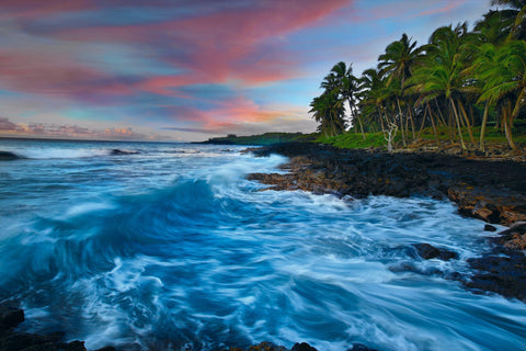 Waves crashing along a palm tree lined rock coast of the Big Island Hawaii