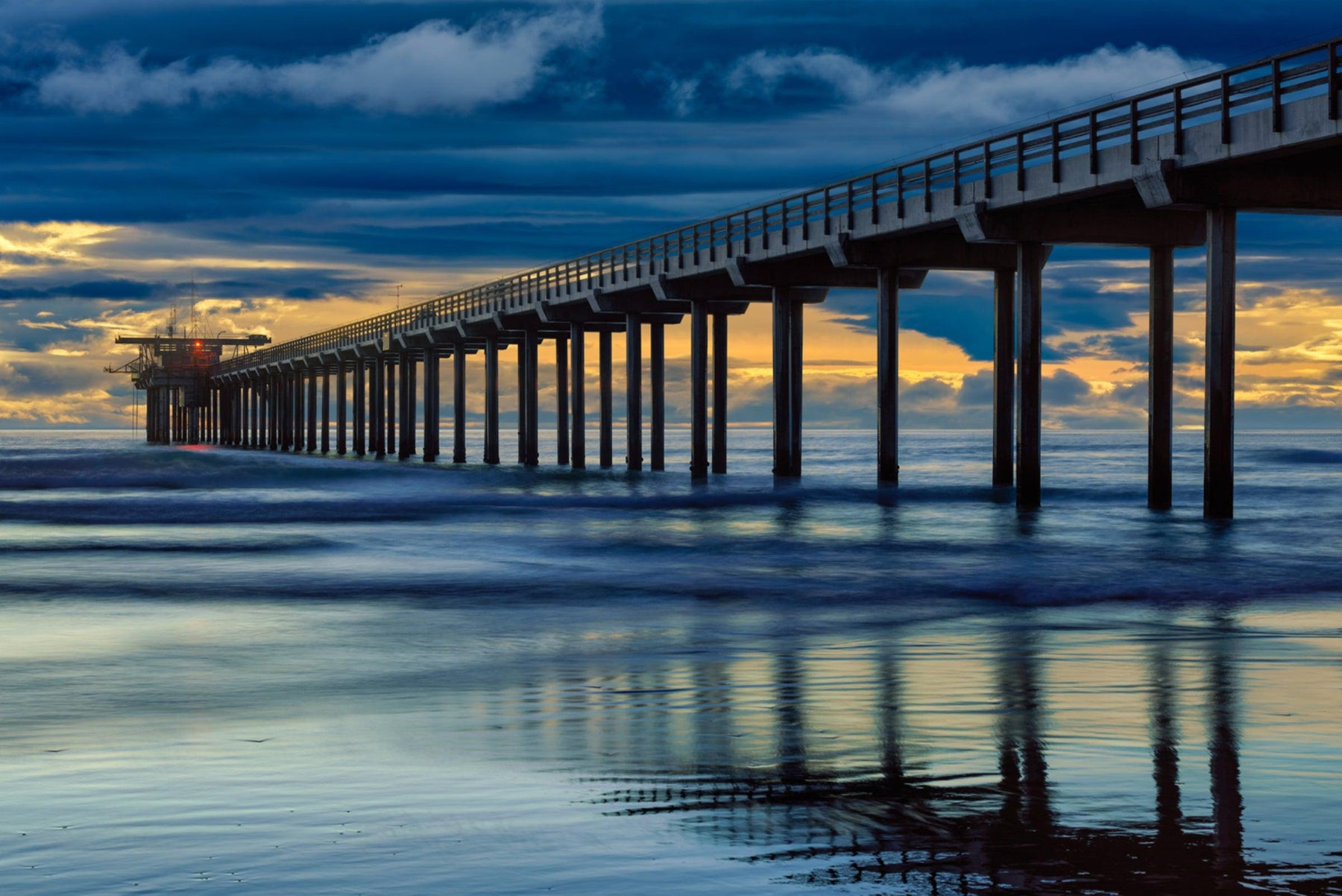 Scipps Pier in California leading off into the ocean under a blue and stormy sky