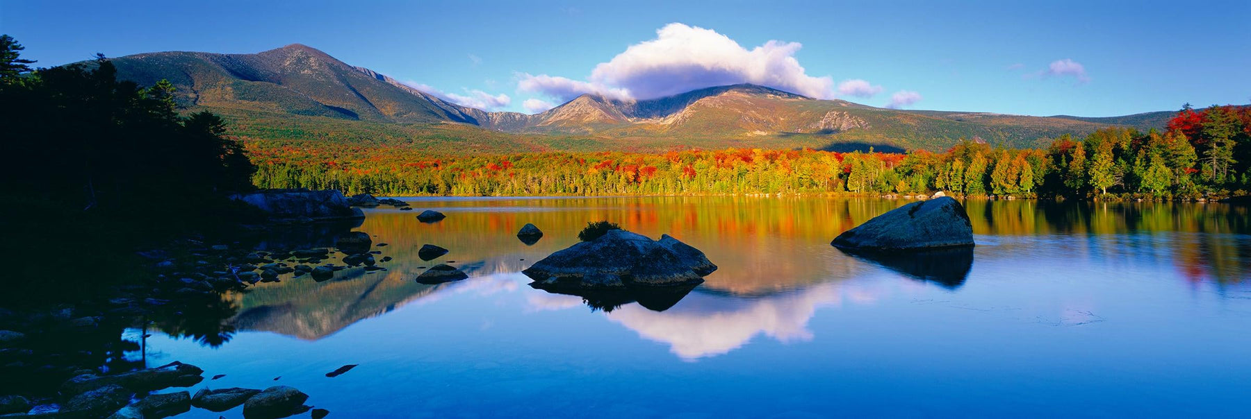 Large rocks near the shore of a lake surrounded by the Autumn colored forest and mountains of Baxter State Park Maine