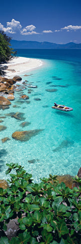 Small boat in the turquoise waters off the rocky shores of Nudey Beach, Australia
