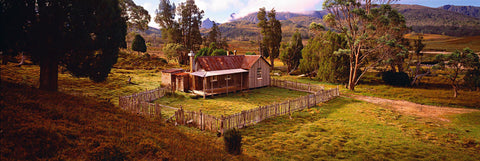 Old wooden shack with a picket fence surrounded by trees in Tasmania, Australia