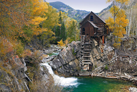Old wooden mill sitting on a rock outcrop above the Crystal River in the forest of Crystal Colorado